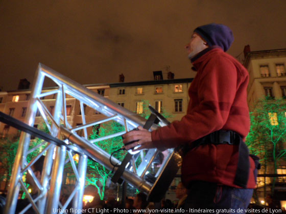 Fête des lumières Lyon - CT Light – Carol Martin & Thibaut Berbézier - Un spectateur joue avec le flipper géant sur la façade du théâtre des Célestins