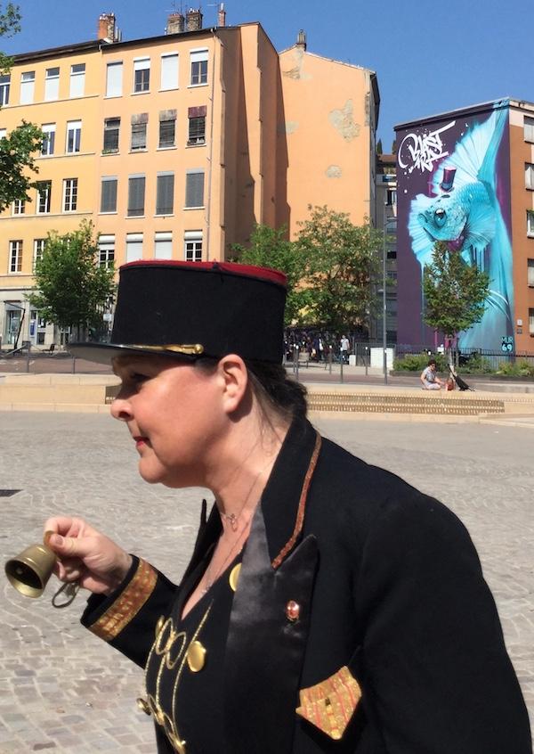 La crieuse publique bat le rappel place des Tapis, Lyon